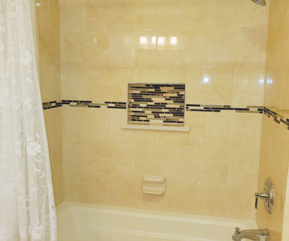 Acclaim Renovations & Design transformed this outdated bathroom by adding quartz tile and a functional niche